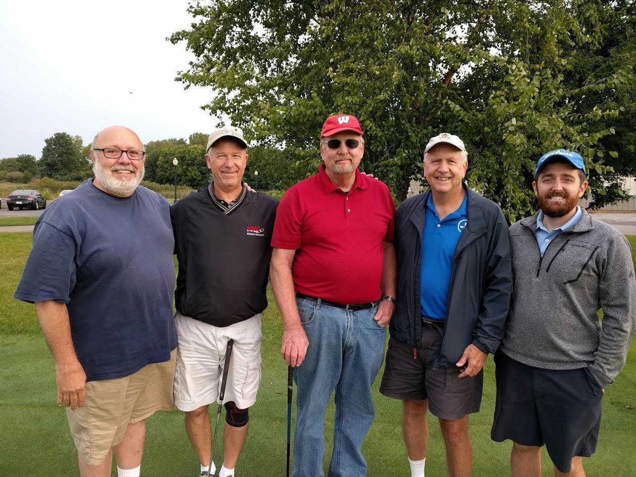 five men smiling together on a golf green
